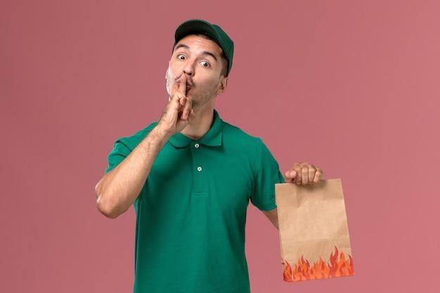 Mensageiro masculino de uniforme verde segurando um pacote de comida pedindo para ficar em silêncio sobre um fundo rosa claro.