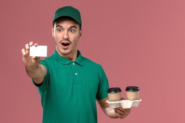 Mensageiro masculino de uniforme verde segurando xícaras de café marrom e um cartão branco na mesa rosa masculino