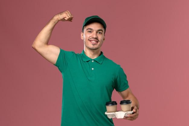 Mensageiro masculino de uniforme verde segurando xícaras de café marrom flexionando em fundo rosa