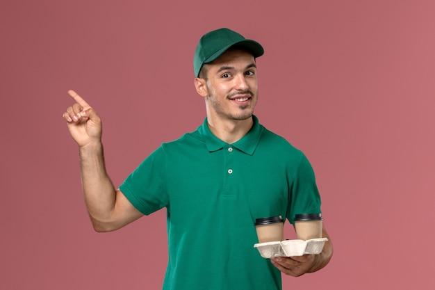 Mensageiro masculino de uniforme verde segurando xícaras de café marrons com um sorriso na mesa rosa