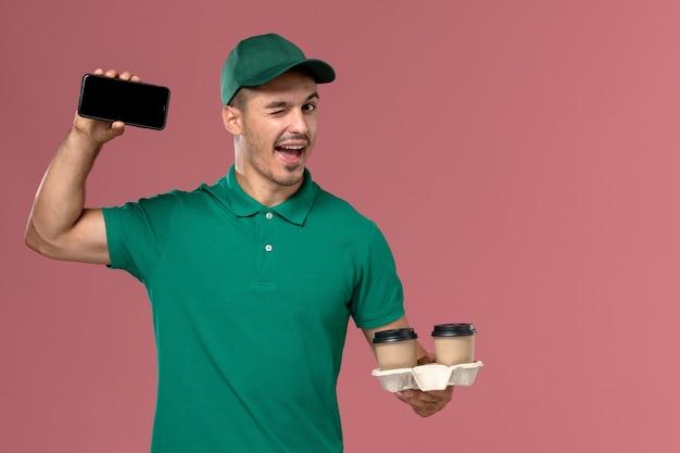Mensageiro masculino de uniforme verde segurando xícaras de café marrons e o telefone piscando na mesa rosa
