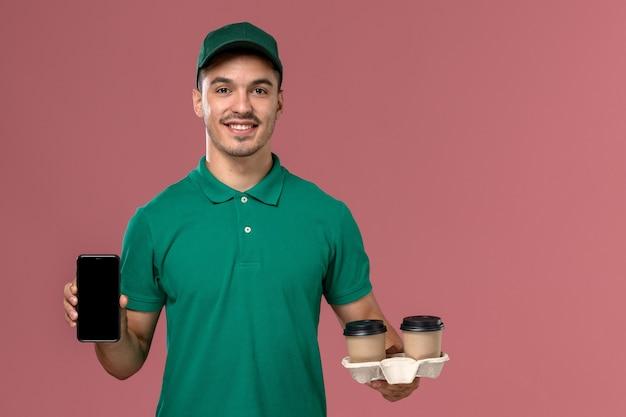 Mensageiro masculino de uniforme verde segurando xícaras de café marrons e um telefone na mesa rosa