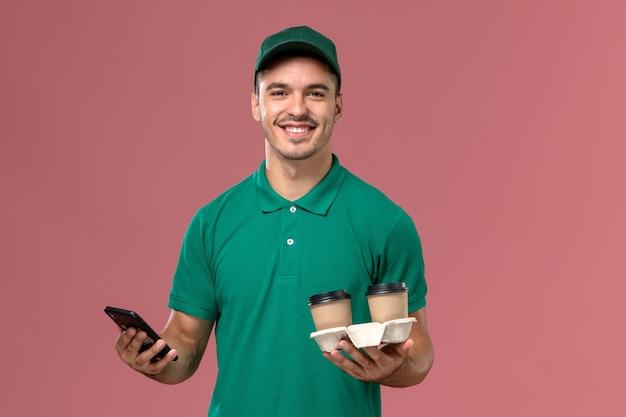 Mensageiro masculino de uniforme verde segurando xícaras de café marrons e usando um telefone com um sorriso na mesa rosa