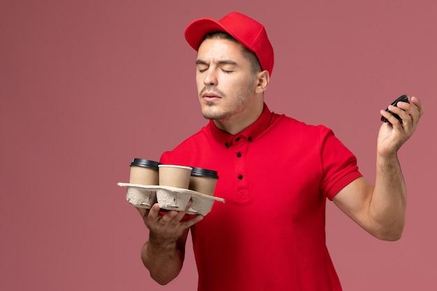 Mensageiro masculino de uniforme vermelho segurando xícaras de café marrons cheirando seu perfume na parede rosa