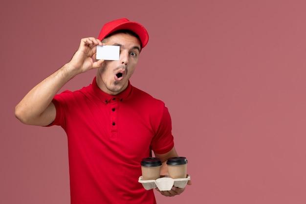Mensageiro masculino de uniforme vermelho segurando xícaras de café marrons com cartão branco na parede rosa