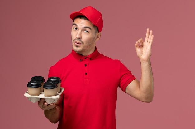 Mensageiro masculino de uniforme vermelho segurando xícaras de café marrons e exibindo sinal de bem na parede rosa