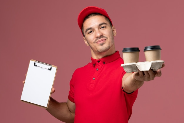 Mensageiro masculino de uniforme vermelho segurando xícaras de café marrons e um bloco de notas na parede rosa claro masculino