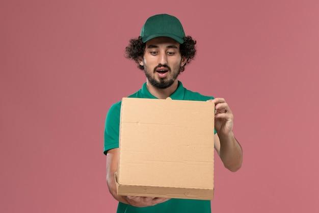 Mensageiro masculino de vista frontal com uniforme verde e capa segurando a caixa de entrega de comida abrindo-a no fundo rosa.