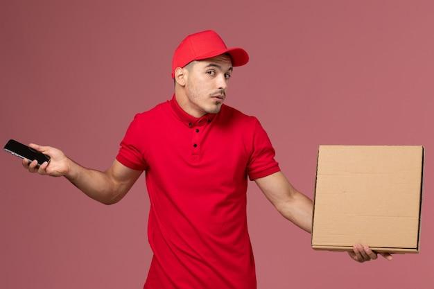 Mensageiro masculino de vista frontal com uniforme vermelho e capa segurando o telefone e a caixa de comida na parede rosa.