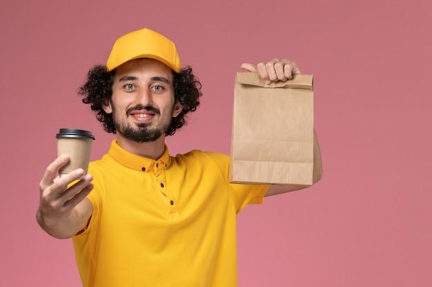 Mensageiro masculino em uniforme amarelo e capa segurando o pacote de comida da xícara de café de entrega na parede rosa