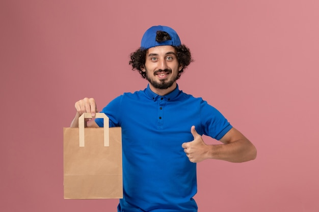 Mensageiro masculino em uniforme azul e capa segurando um pacote de comida de papel de entrega em uniforme de serviço de entrega de trabalho de parede rosa