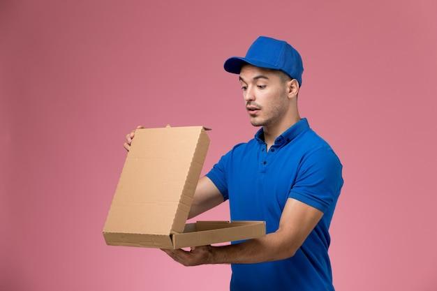 Mensageiro masculino em uniforme azul segurando e abrindo a caixa de comida rosa, serviço de entrega de uniforme de trabalhador