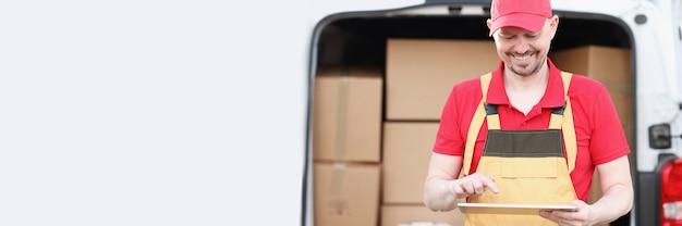 Mensageiro masculino em uniforme fica perto do carro com caixas e segura o tablet