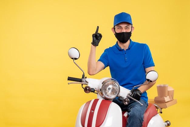 Mensageiro masculino sentado em uma bicicleta, mascarado, com uniforme de serviço secreto de trabalho de entrega de pandemia amarela