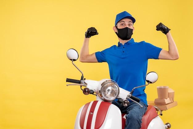 Mensageiro masculino sentado em uma bicicleta, mascarado em um serviço de trabalho amarelo, pandemia de entrega covid