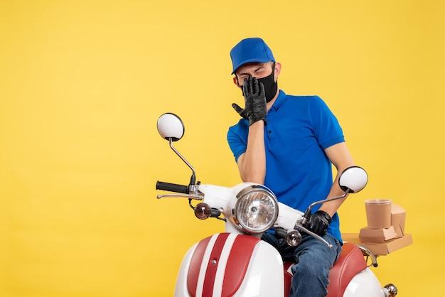 Mensageiro masculino sentado em uma bicicleta, mascarado, no trabalho de entrega de pandemia amarela, serviço secreto