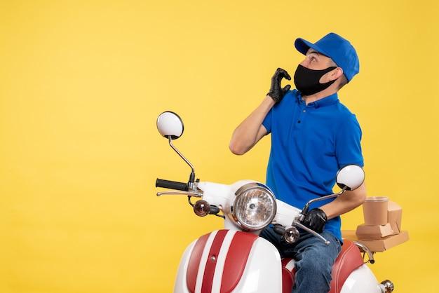 Mensageiro masculino sentado na bicicleta, mascarado, assustado com a pandemia amarela, trabalho de entrega secreta - uniforme de serviço