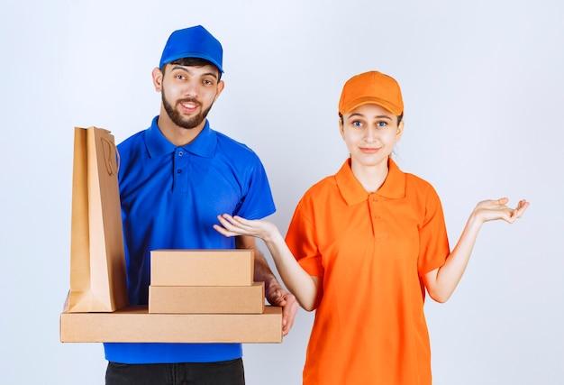 Mensageiro menino e menina em uniformes azuis e amarelos segurando caixas de papelão para viagem e pacotes de compras.