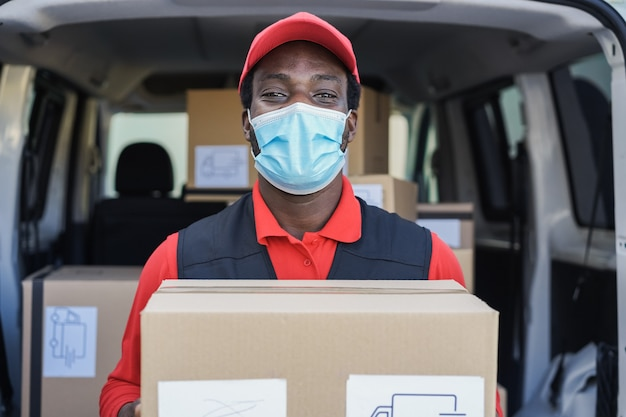 Mensageiro negro entregando pacote na frente do caminhão de carga usando máscara de segurança - foco no rosto