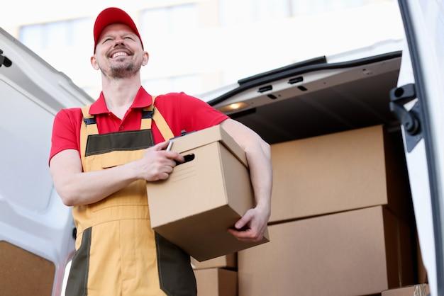 Mensageiro sorridente segurando uma grande caixa de papelão