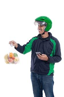 Mensageiro usando capacete e uniforme de jaqueta segurando comida isolada sobre fundo branco