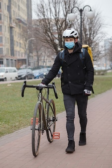 Mensageiro usando máscara médica, andando de bicicleta e carregando mochila térmica