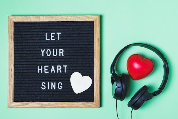 Mensagem a bordo; coração vermelho e fone de ouvido sobre fundo verde