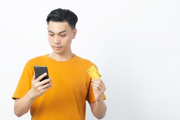 Mensagem asiática feliz nova da leitura do homem do smartphone e cartão de crédito guardar com copyspace no branco.