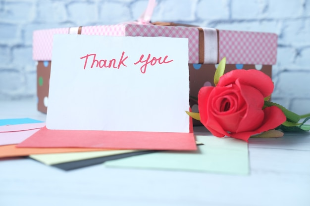 Mensagem de agradecimento e envelope na mesa de madeira