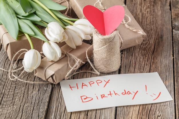 Mensagem de feliz aniversário com flores na mesa rústica com flores