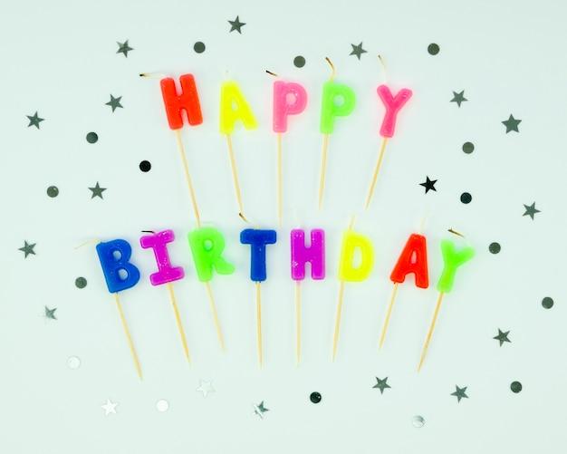 Mensagem de feliz aniversário com velas coloridas e confetes