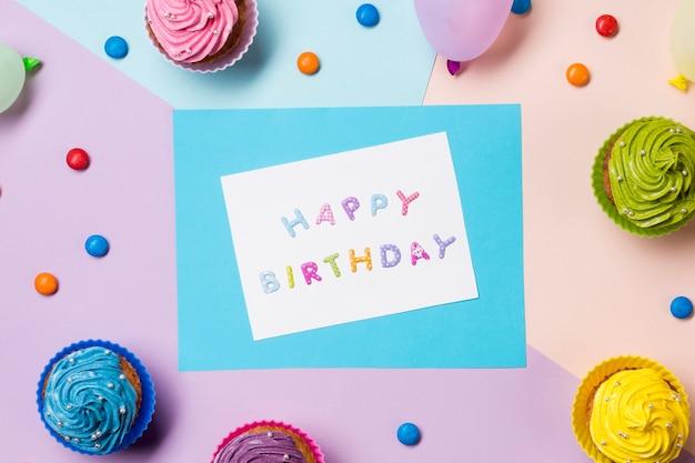 Mensagem de feliz aniversário em papel branco, rodeado de pedras preciosas e muffins em pano de fundo colorido