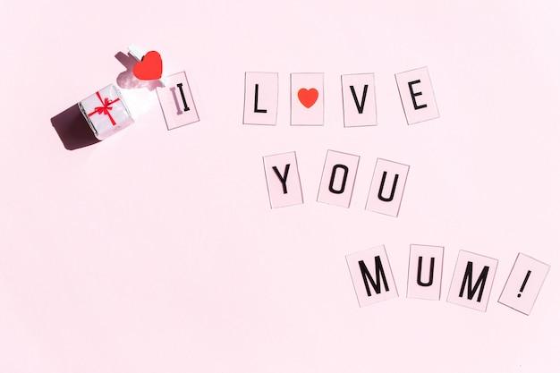 Mensagem de feliz dia das mães com corações vermelhos em fundo rosa brilhante. conceito de cartão de saudação. mensagem do dia das mães. presente e texto