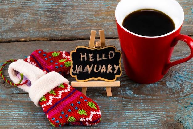 Mensagem de janeiro do conceito olá! no quadro-negro com uma xícara de café e luvas