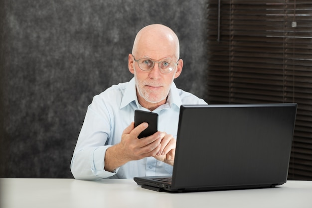 Mensagem de leitura do homem de negócios sênior para smartphone