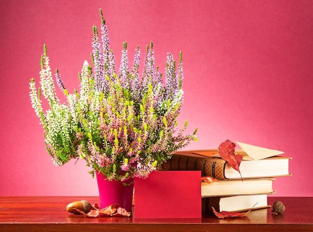 Mensagem de outono. natureza morta com cartão vermelho em branco, envelope, flores de urze, folhas secas e livros
