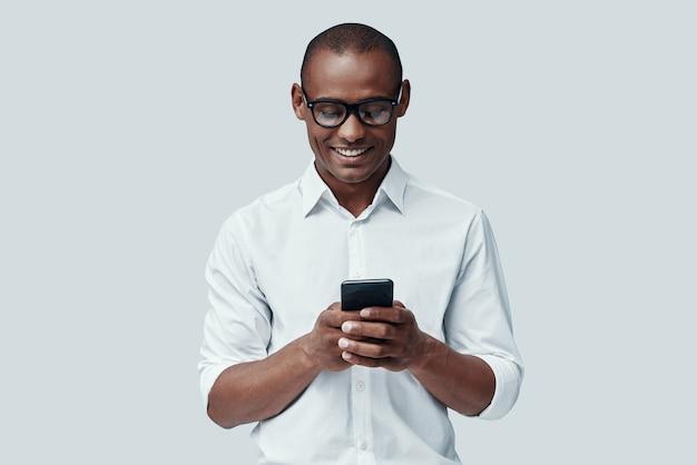 Mensagem de texto. africano jovem e bonito usando um telefone inteligente em pé contra um fundo cinza