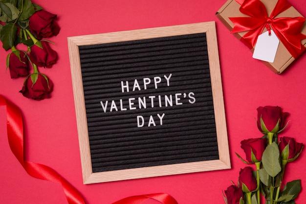Mensagem do dia de valentim na placa de letra com fundo romântico vermelho, rosas e presente.