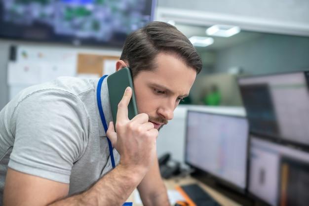 Mensagem importante. jovem barbudo atento trabalhando em uma sala especialmente equipada, recebendo informações importantes por smartphone