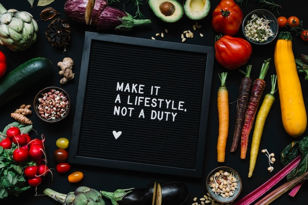 Mensagem no quadro preto rodeado de legumes contra o pano de fundo preto