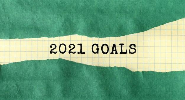 Mensagem objetivos 2021 escrita sob papel rasgado verde. conceito.