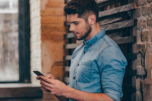 Mensagem para ela. vista lateral de um jovem pensativo bonito segurando um telefone inteligente e olhando para ele enquanto se inclina para uma parede de tijolos no interior do loft