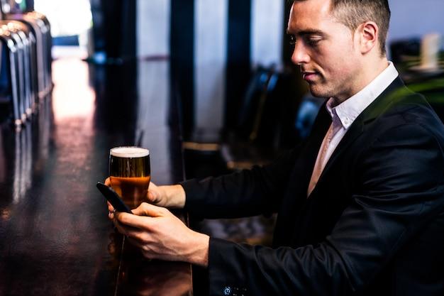 Mensagens de empresário e tomando uma cerveja em um bar