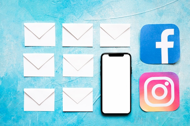 Mensagens de envelope branco papel e ícone de mídia social com celular em fundo azul