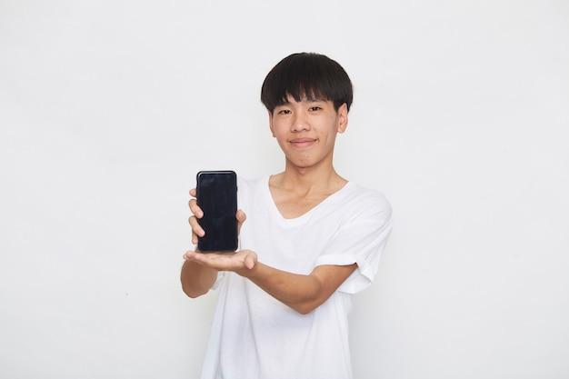 Mensagens de mensagens de texto de estudante bonito jovem asiático usando o smartphone em uma superfície leve. copie o espaço e a maquete