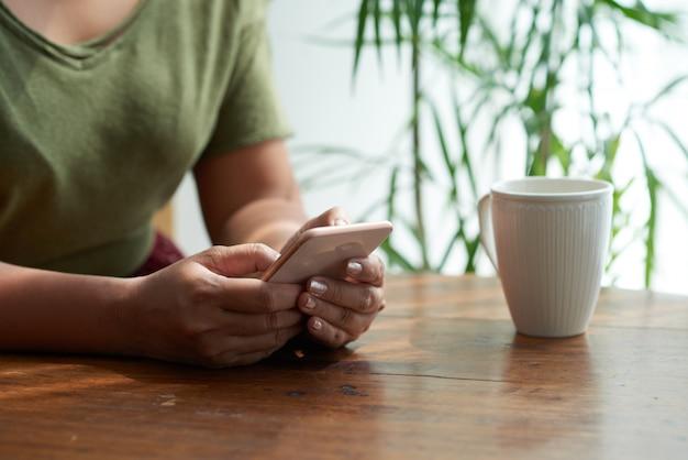 Mensagens de texto com um amigo no cosy cafe