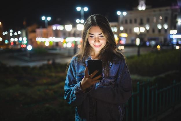 Mensagens de texto de garota linda no celular ao ar livre sobre a parede da rua à noite borrada, foco seletivo