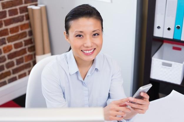 Mensagens de texto executivas femininas sorridentes no escritório
