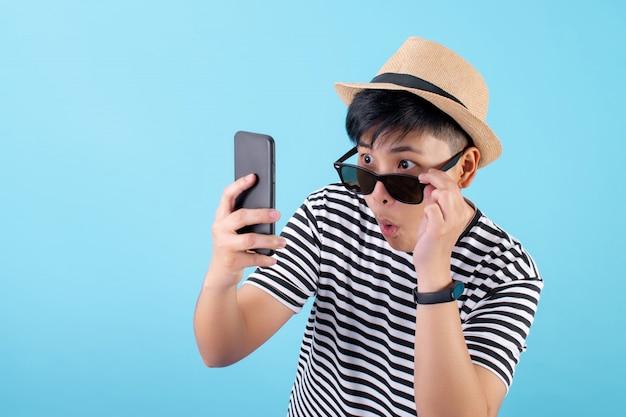 Mensagens felizes e chocadas de turista asiático no smartphone em um fundo azul
