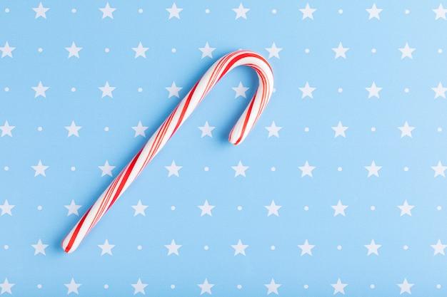 Menta o bastão de doces duros listrado nas cores do natal isoladas em um fundo azul com estrelas. natal, inverno, ano novo conceito.